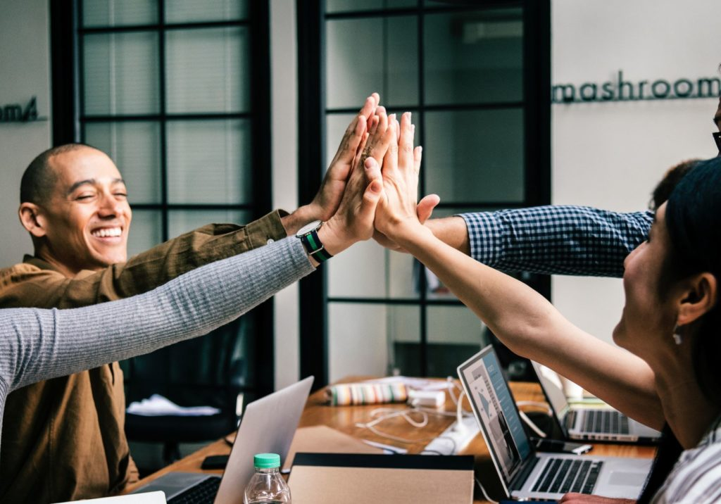 Four people high-fiving eachother around a work table.